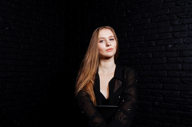 Studioschot van donkerbruin meisje in zwarte blouse met bustehouder en borrels tegen zwarte bakstenen muur.