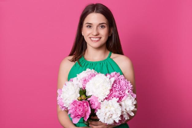 Studioschot van het leuke donkerbruine europese vrouwelijke stellen geïsoleerd over roze