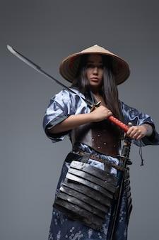 Studioschot van vrouwensamoerai die kimono en hoed draagt die katana houden tegen grijze achtergrond.