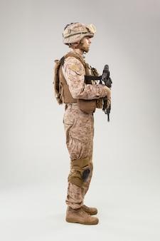 Studiospruit van moderne infanteriemilitair, mariene rifleman van de vs in gevechtsuniform, helm en kogelvrije vesten