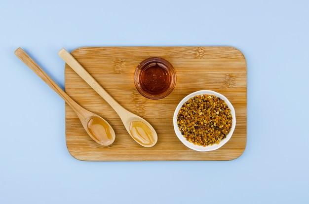 Stuifmeel met honing en houten lepels op kast