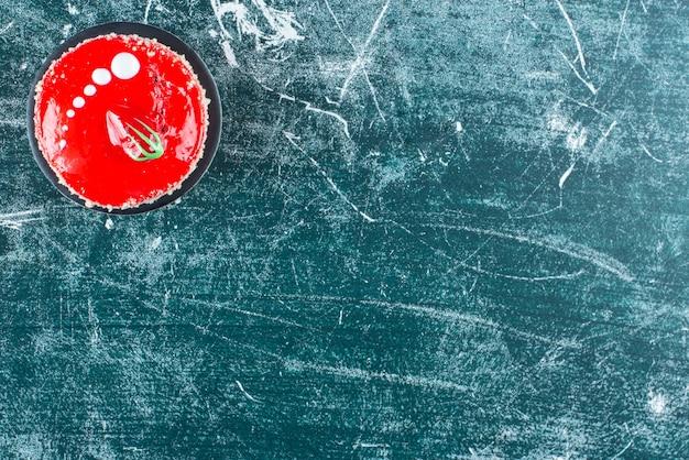 Stuk aardbeientaart op marmeren tafel.
