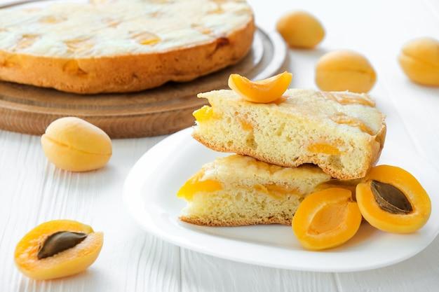 Stuk abrikozentaart op bord met volle cake gezonde voeding veganistisch dessert glutenoff