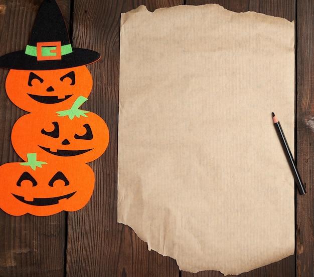 Stuk bruin papier en oranje pompoenviltfiguren