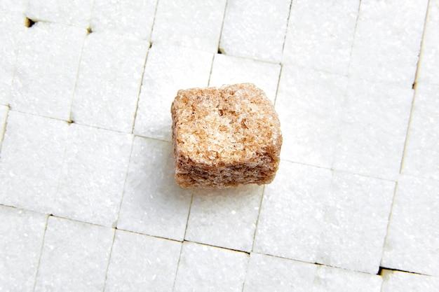 Stuk bruin riet ongeraffineerde suiker opleggen van witte suikerklontjes