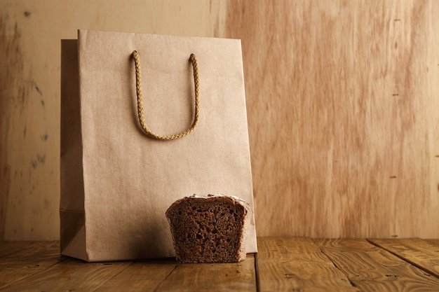 Stuk bruin roggebrood dat dichtbij wordt gepresenteerd haalt lege zak weg van ambachtelijk papier in ambachtelijke bakkerij op houten achtergrond