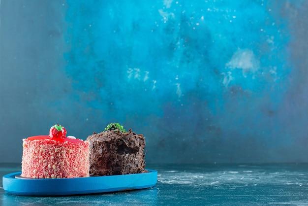 Stuk chocolade en aardbeicakes op blauw bord.
