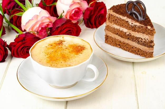 Stuk chocoladetaart, cappuccino, bloemen op tafel.