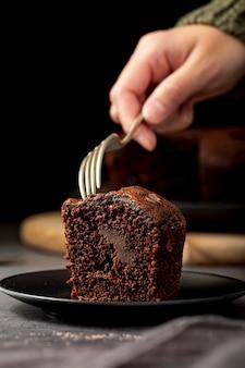 Stuk chocoladetaart in een zwarte plaat