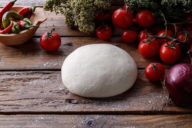 Stuk deeg op een houten tafel, omringd met tomaten, paprika en een ui
