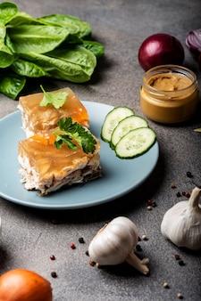 Stuk eigengemaakte gelei met vlees op de plaat. aspic gevogelte en rundvlees, traditionele russische en oekraïense schotel met mosterd, kruiden en verschillende ingrediënten. holodets