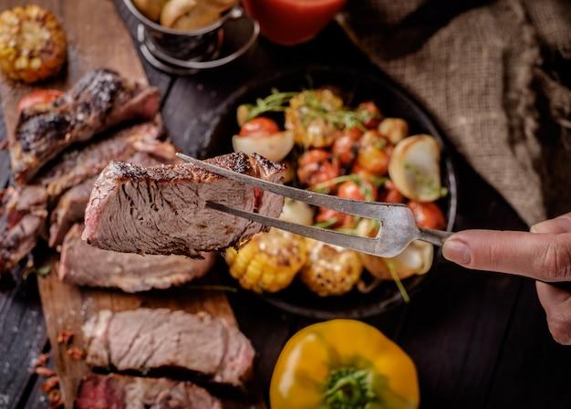 Stuk gegrilde biefstuk op een vork.