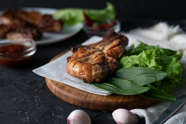 Stuk gekookte geroosterde varkensfilet met slabladeren, ui en saus, rommel