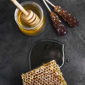Stuk honingraat; honingpot en honing beer op zwarte textuur achtergrond
