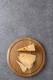 Stuk kaas en plakjes op een keukenbord close-up, bovenaanzicht
