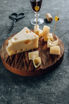 Stuk koemelk maasdammer kaas op houten snijplank over betonnen achtergrond.