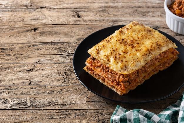 Stuk lasagne op een zwarte plaat op rustieke houten tafel