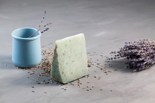 Stuk lavendelkaas omgeven door lavendelbloemen op grijze achtergrond.