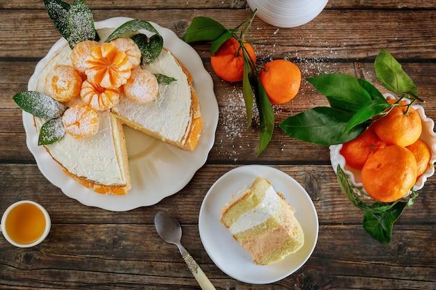 Stuk mandarijnbiscuitgebak versierd met hele verse mandarijnen