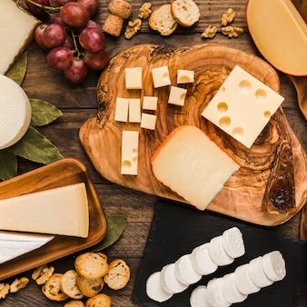 Stuk natuurlijke kazen op kaasplank met smakelijk ingrediënt over houten bureau