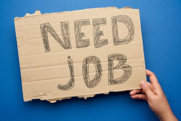Stuk papier met de inscriptie moet baan, concept van werkloosheid