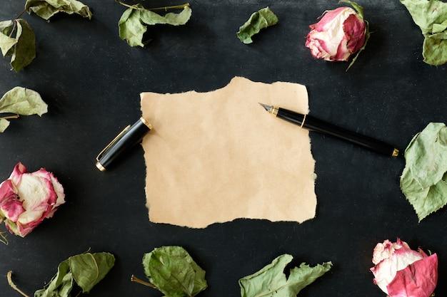 Stuk papier met stylus pen en gedroogde rozen en bladeren op zwarte achtergrond, bovenaanzicht