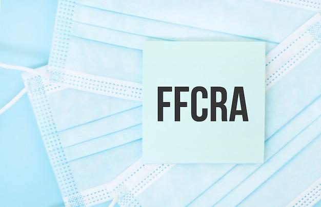 Stuk papier met zin ffcra op stapel blauwe medische maskers. coronavirus pandemie concept