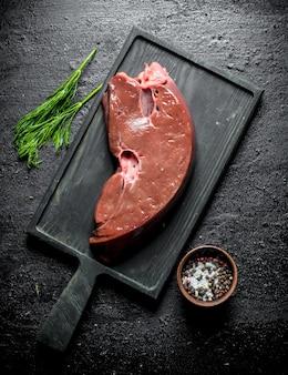 Stuk rauwe lever op een snijplank met dille en kruiden. op zwarte rustieke ondergrond