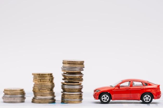 Stuk speelgoed auto dichtbij de stijgende stapel muntstukken tegen witte achtergrond