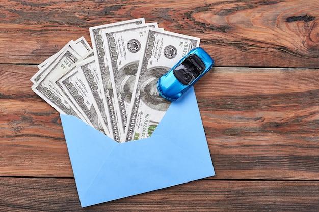 Stuk speelgoed auto en amerikaanse dollars. geld in envelop en auto. geniet van materiële rijkdom.