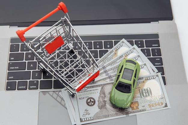 Stuk speelgoed auto en boodschappenwagentje met geld op laptop. online aankoop auto concept.