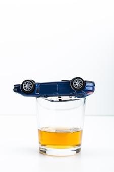 Stuk speelgoed auto en glas van de crashongeval van de whiskymetafoor op wit wordt geïsoleerd dat