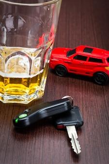 Stuk speelgoed auto en glas van geïsoleerd de neerstortingsongeval van de whiskymetafoor