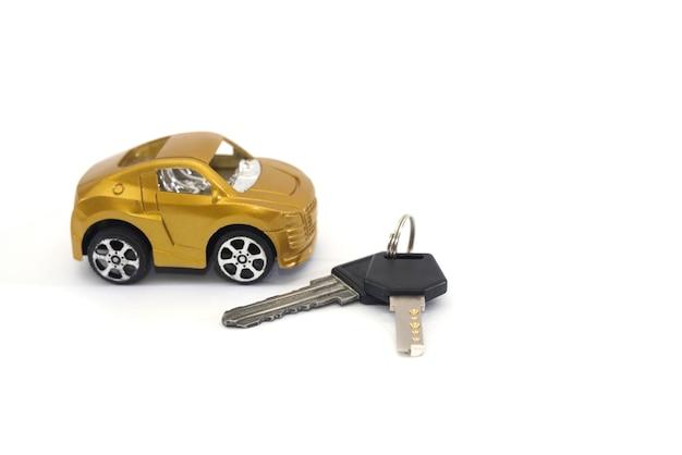 Stuk speelgoed auto en sleutels die op witte achtergrond worden geïsoleerd. auto aankoop concept.