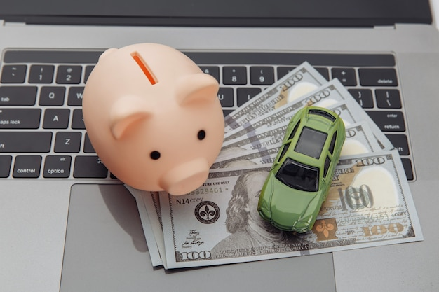 Stuk speelgoed auto en spaarvarken met geld op laptop
