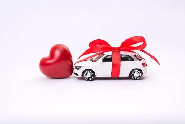 Stuk speelgoed auto met het rood hart van de lintboog