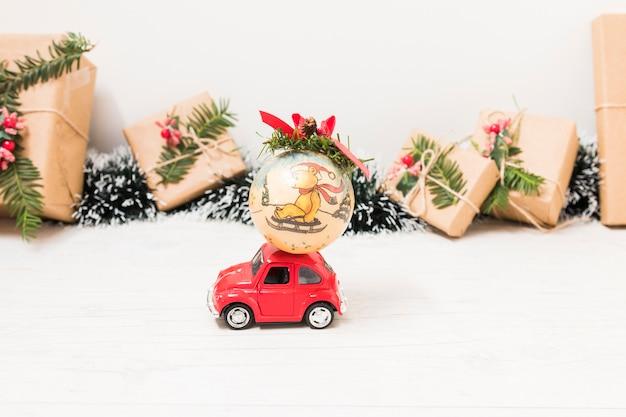 Stuk speelgoed auto met kerstmisbal dichtbij huidige dozen