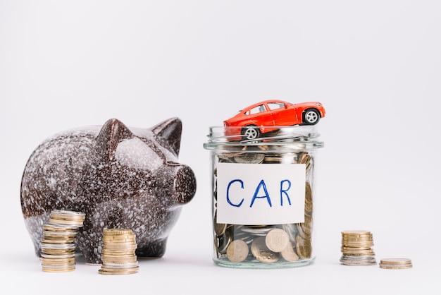 Stuk speelgoed auto over de kruik die met muntstukken en stapel muntstukken en piggybank op witte achtergrond wordt gevuld