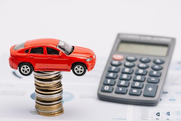 Stuk speelgoed auto over de muntstapel met calculator op rapport