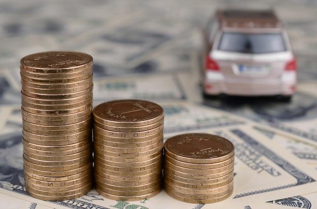 Stuk speelgoed automodel bij de stapels gouden muntstukken ligt op vele dollarrekeningen