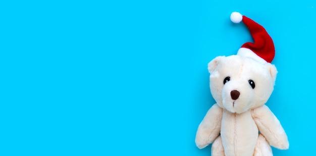 Stuk speelgoed beer met een kerstmuts op blauwe ondergrond