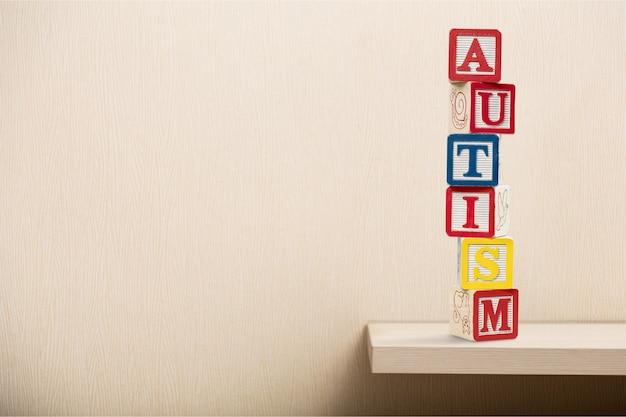 Stuk speelgoed blokken met woord autisme over lichte achtergrond