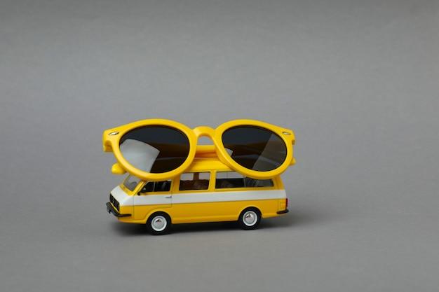 Stuk speelgoed bus met gele zonnebril op grijze geïsoleerde achtergrond