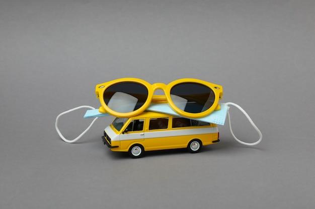 Stuk speelgoed bus met zonnebril en masker op grijze geïsoleerde achtergrond
