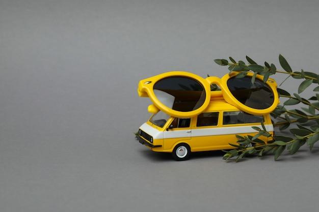 Stuk speelgoed bus met zonnebril en tak op grijze geïsoleerde achtergrond