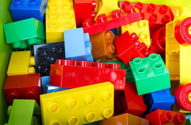 Stuk speelgoed die kleurrijke blokken op groene doos bouwen.