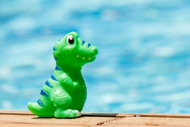 Stuk speelgoed dino die zich bij het zwembad op een zonnige dag bevindt