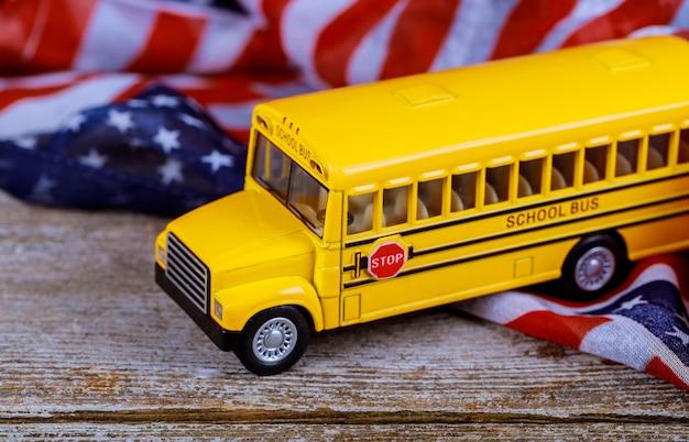 Stuk speelgoed gele schoolbus op amerikaanse vlag