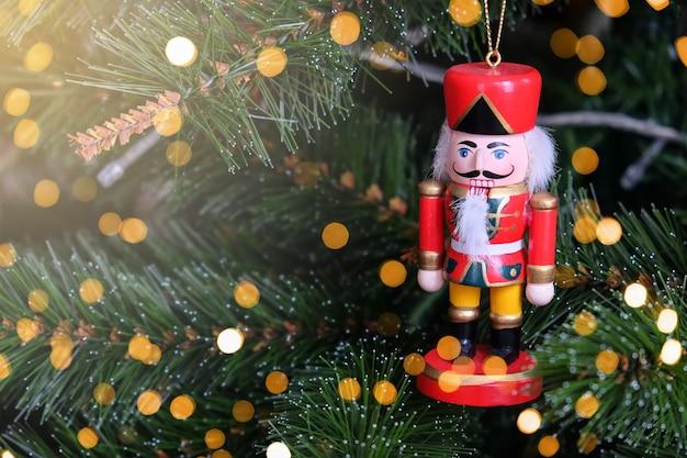 Stuk speelgoed grappige notenkraker die op kerstboom hangen.