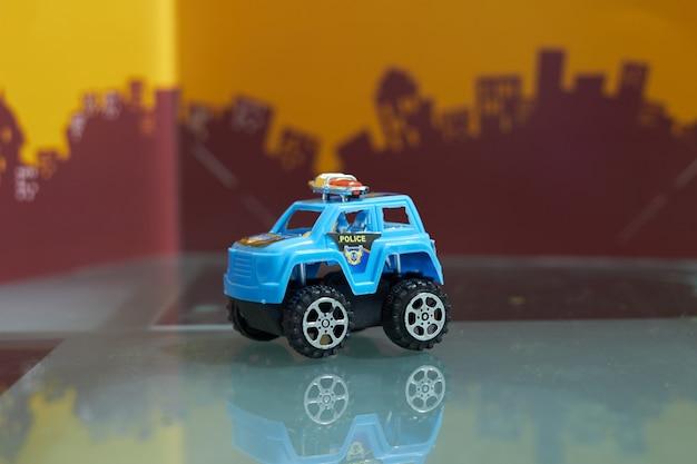 Stuk speelgoed grote wielauto in politieconcept op onduidelijk beeldstad